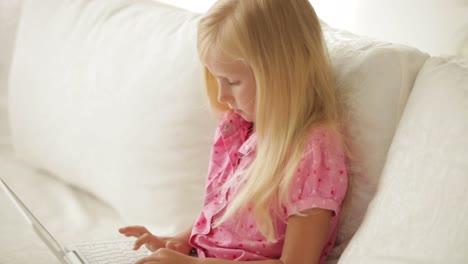 Graciosa-Niña-Sentada-En-El-Sofá-Usando-Laptop-Y-Sonriendo