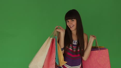 Happy-Girl-Holding-Shopping-Bags-And-Smiling