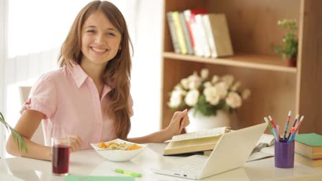 Niña-Feliz-Sentada-En-La-Mesa-Estudiando-Usando-La-Computadora-Portátil-Mirando-A-Cámara-Y-Sonriendo