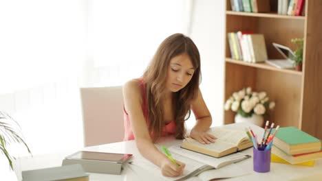 Feliz-Niña-Sentada-En-La-Mesa-Estudiando-Escribir-En-El-Libro-De-Trabajo-Mirando-A-La-Cámara
