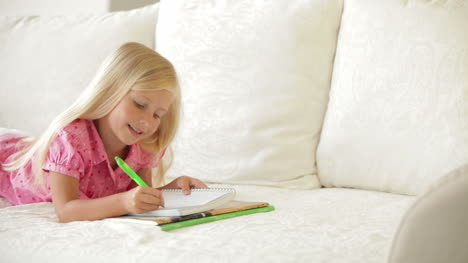 Happy-Little-Girl-Lying-On-Couch-Writing-In-Notebook-And-Smiling