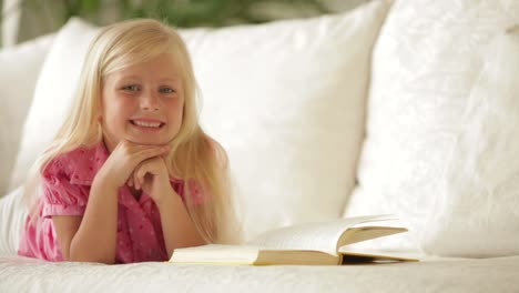 Happy-Little-Girl-Lying-On-Sofa-With-Book-And-Smiling-At-Camera