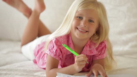 Happy-Little-Girl-Lying-On-Sofa-Writing-In-Notebook-And-Smiling