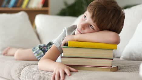 Little-Boy-Lying-On-Sofa-With-Stack-Of-Books