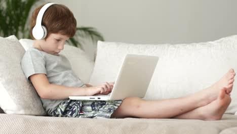 Niño-Relajado-En-El-Sofá-Y-Usando-Laptop