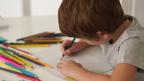 Kleiner-Junge-Sitzt-Am-Tisch-Und-Zeichnet-Mit-Buntstiften