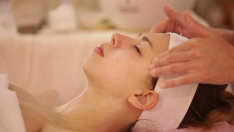 Massage-Specialist-Massaging-Woman-s-Face-At-Beauty-Salon-Panning-Camera