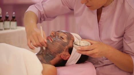 Massage-Therapist-Applying-Cosmetic-Mask-On-Female-Face-At-Beauty-Salon-Panning