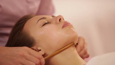 Massage-Therapist-Doing-Massage-Of-Female-Face-With-Bamboo-Stick-At-Beauty
