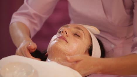 Massage-Therapist-Doing-Professional-Massage-Of-Female-Face-Panning-Camera