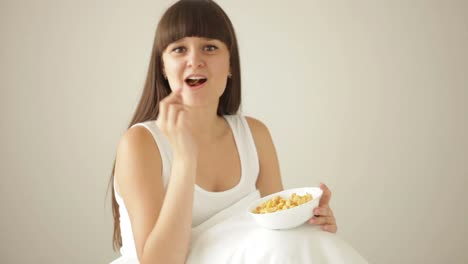 Pretty-Girl-Sitting-On-Bed-Eating-Cereal-And-Smiling-At-Camera