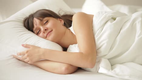 Pretty-Girl-Sleeping-In-Bed-Hugging-Her-Pillow-And-Smiling-In-Her-Sleep