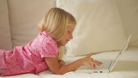 Niña-Bonita-Descansando-En-El-Sofá-Usando-Laptop-Y-Sonriendo-A-La-Cámara
