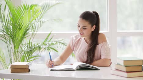 Pretty-Student-Girl-Studying-At-Table-With-Books-And-Smiling-At-Camera