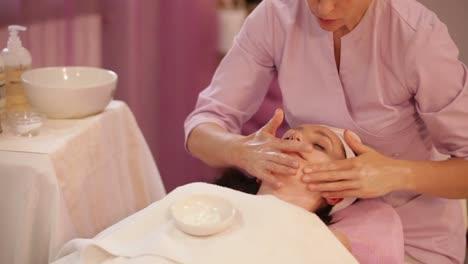 Esteticista-Profesional-Haciendo-Masaje-De-Rostro-Femenino-En-Salón-De-Belleza