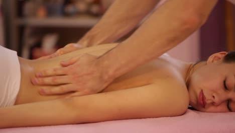 Masajista-Profesional-Haciendo-Masaje-De-Espalda-Femenina-En-Salón-De-Belleza