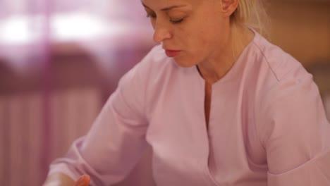 Masajista-Profesional-Masajeando-El-Rostro-Femenino-En-La-Panorámica-Del-Salón-De-Belleza