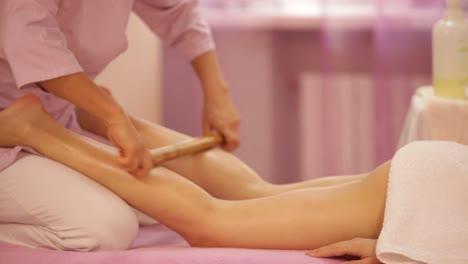 Professional-masseuse-doing-massage-of-woman-with-bamboo-stick