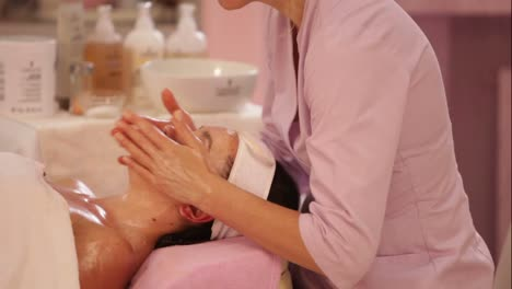 Professional-Masseuse-Doing-Massage-Of-Woman-s-Face-At-Beauty-Spa