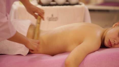 Professional-Masseuse-Massaging-Female-Back-With-Bamboo-Stick-At-Beauty-Salon