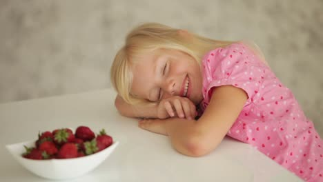 Sleepy-Little-Girl-Sitting-At-Table-And-Eating-Strawberries