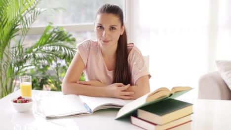 Chica-Estudiante-Sentada-En-La-Mesa-Rodeada-De-Libros-Y-Sonriendo-A-La-Cámara