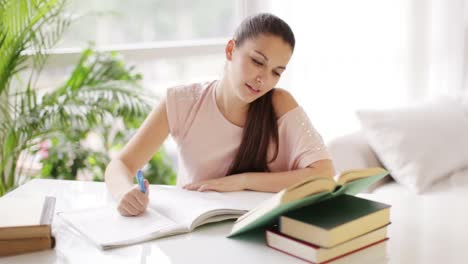 Student-Girl-Studying-At-Table-With-Books-And-Smiling