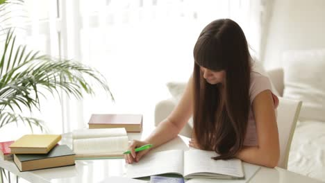 Student-Girl-Studying-At-Table-Writing-In-Notebook-And-Smiling