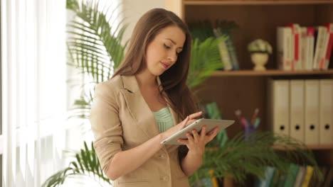 Atractiva-Empresaria-De-Pie-Delante-De-La-Ventana-Con-Touchpad-Y-Sonriendo