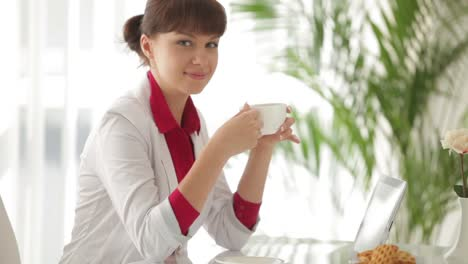 Attractive-Girl-Sitting-At-Table-Drinking-Tea-And-Using-Tablet
