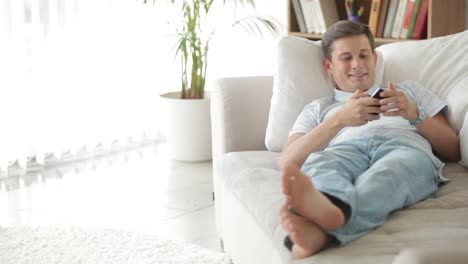 Atractivo-Joven-Tumbado-En-El-Sofá-Con-Teléfono-Móvil-Y-Sonriendo