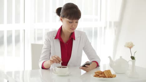 Attractive-Young-Woman-Sitting-At-Table-With-Cup-Of-Tea-And-Using-Cellphone