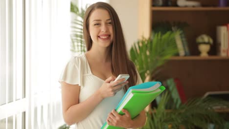 Attractive-Young-Woman-Standing-Holding-Paper-Folders-Smiling-And-Using-Phone