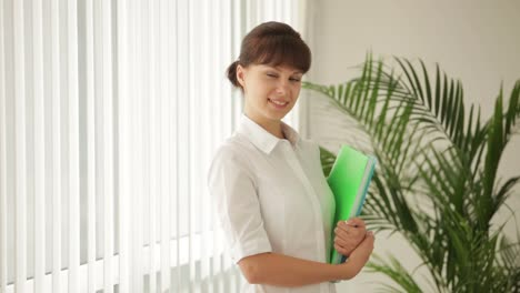 Beautiful-Business-Woman-Standing-In-Front-Of-Window-Holding-Paper-Folders