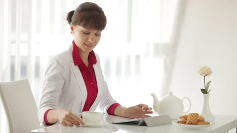 Beautiful-Woman-Sitting-At-Table-With-Cup-Of-Tea-And-Using-Tablet