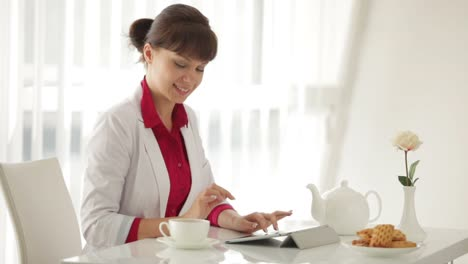 Beautiful-Young-Woman-Sitting-At-Table-Drinking-Tea-And-Using-Tablet