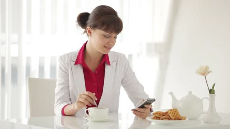 Beautiful-Young-Woman-Sitting-At-Table-With-Cup-Of-Tea-And-Using-Cellphone