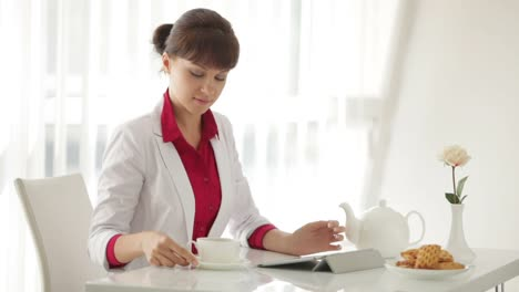 Beautiful-Young-Woman-Sitting-At-Table-With-Cup-Of-Tea-And-Using-Tablet