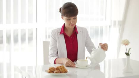 Charming-Girl-Sitting-At-Table-And-Pouring-Tea
