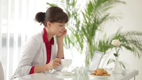 Charming-Girl-Sitting-At-Table-Drinking-Tea-And-Using-Tablet