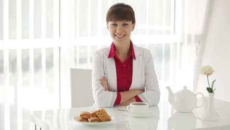 Charming-Girl-Sitting-At-Table-With-Tea-And-Smiling