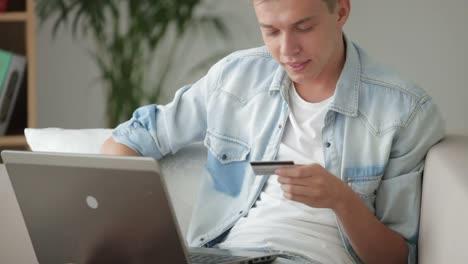 Schöner-Mann-Der-Sich-Mit-Laptop-Auf-Dem-Sofa-Entspannt-und-Kreditkarte-Hält