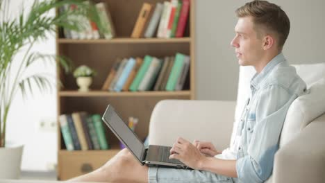 Handsome-Student-Relaxing-On-Sofa-With-Laptop
