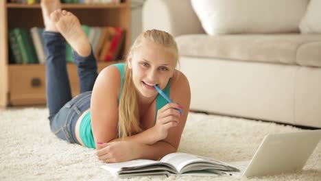 Happy-Girl-Relaxing-On-Carpet-With-Notebook