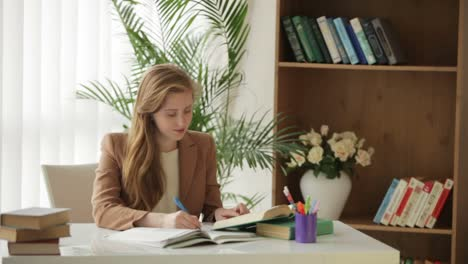 Pretty-Girl-Sitting-At-Desk-With-Books-Writing-In-Workbook-Looking-At-Camera