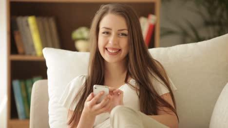 Hübsches-Mädchen-Das-Auf-Dem-Sofa-Sitzt-Und-Lächelt-Und-Handy-Benutzt