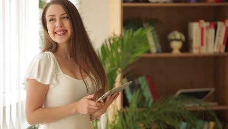 Linda-Chica-De-Pie-Con-Touchpad-Mirando-A-Cámara-Y-Sonriendo