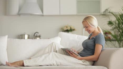 Hübsche-Junge-Frau-Die-Sich-Auf-Dem-Sofa-Mit-Touchpad-Entspannt-Und-In-Die-Kamera-Lächelt