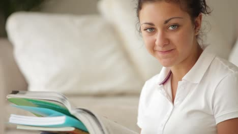 Smiling-Student-Girl-Sitting-With-Books-Studying-And-Writing-In-Notebook