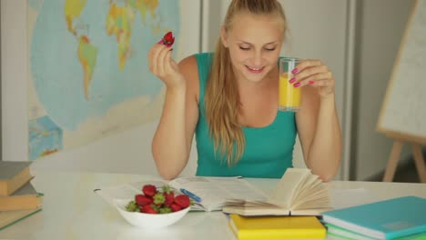 Young-Girl-Sitting-At-Table-Eating-Strawberry-And-Drink-Juice
